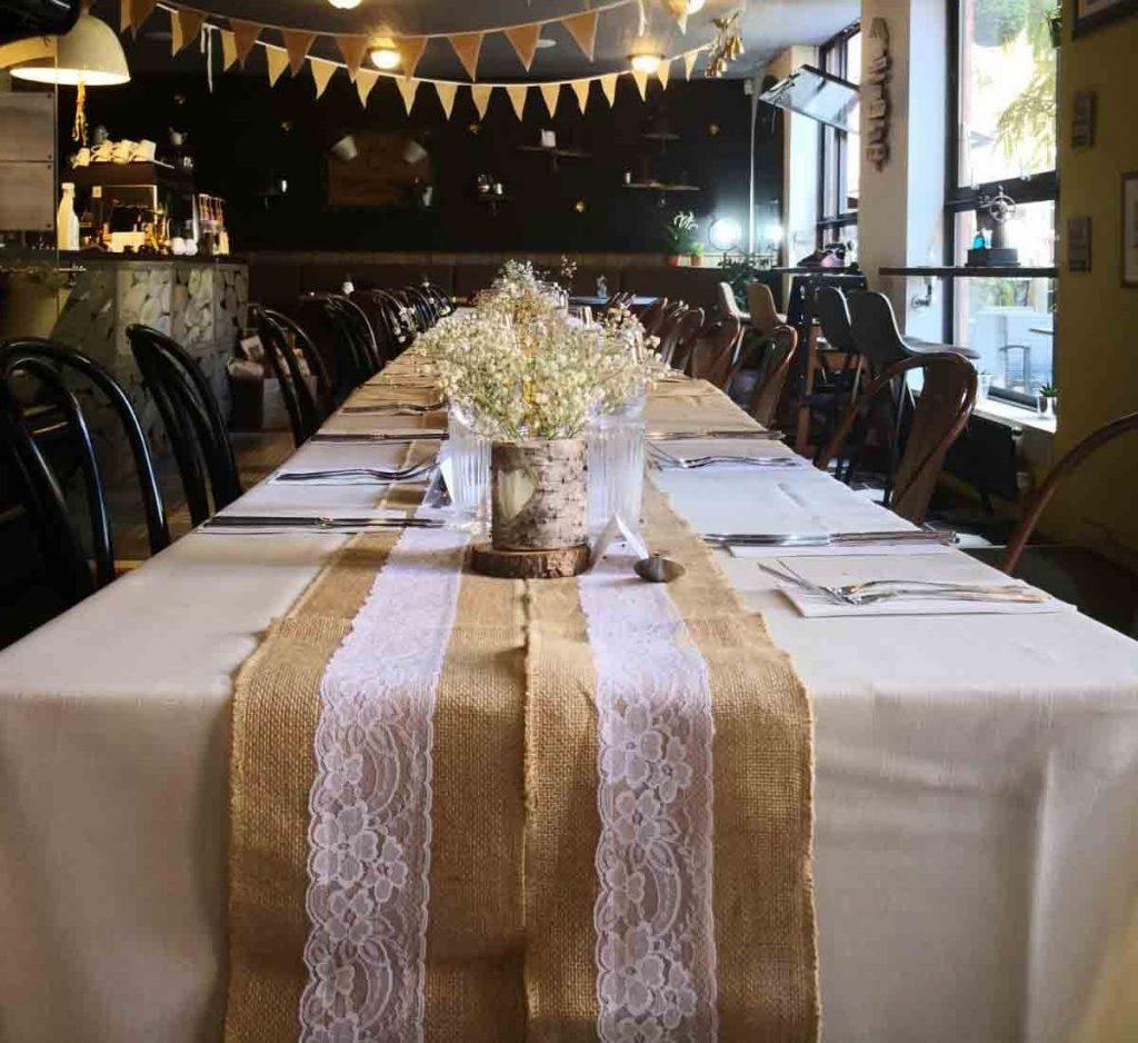 A long table decorated in white and gold cloth with fresh flowers, spanning the length of Bayley Lane