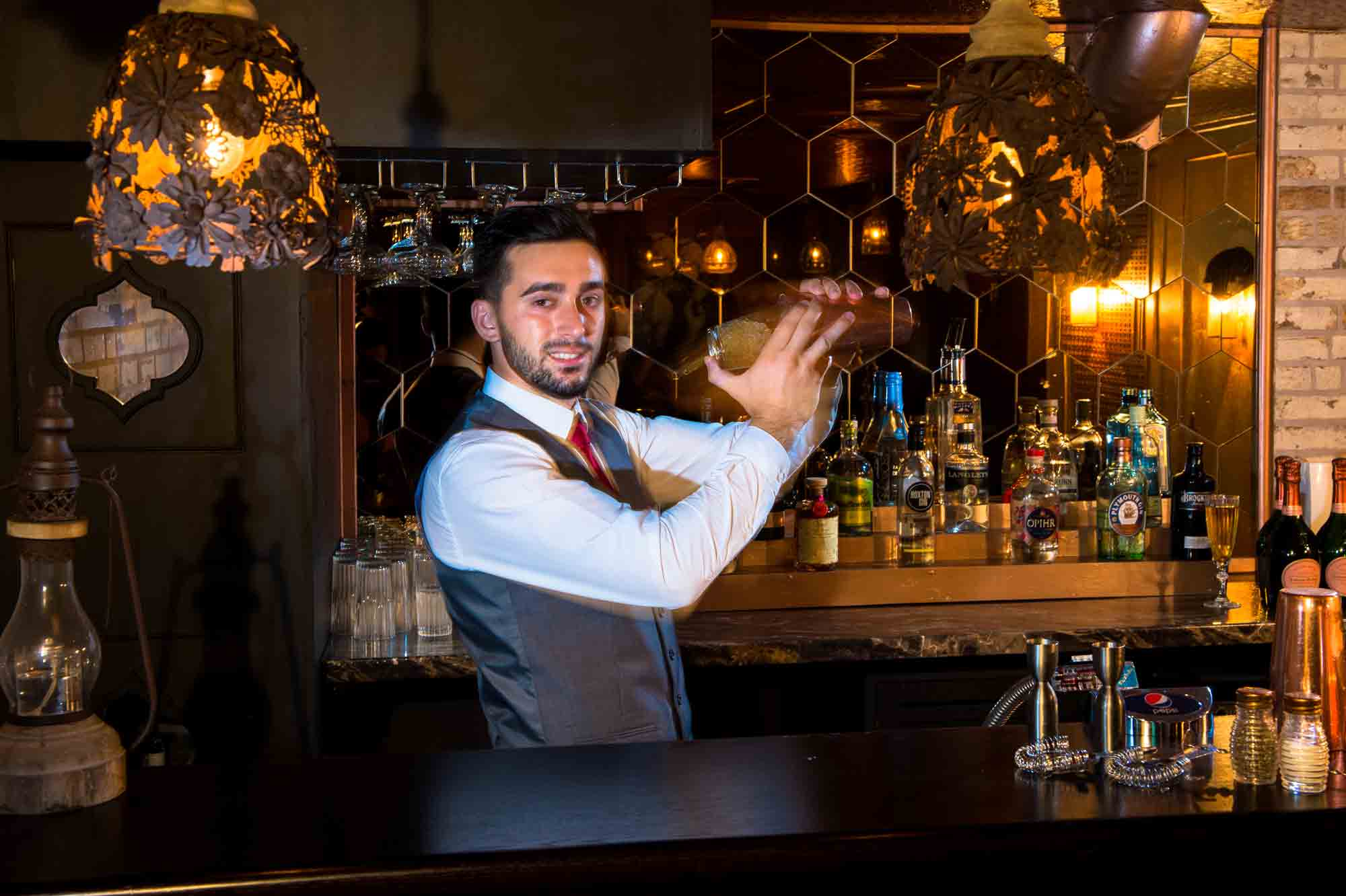 Well dressed barman mixing cocktails at a classy bar in front of a liquor display.