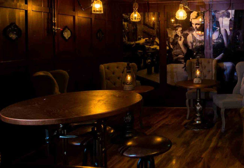 A dark vintage themed room, full of antique Oak furniture. Being lit by vintage light fittings.